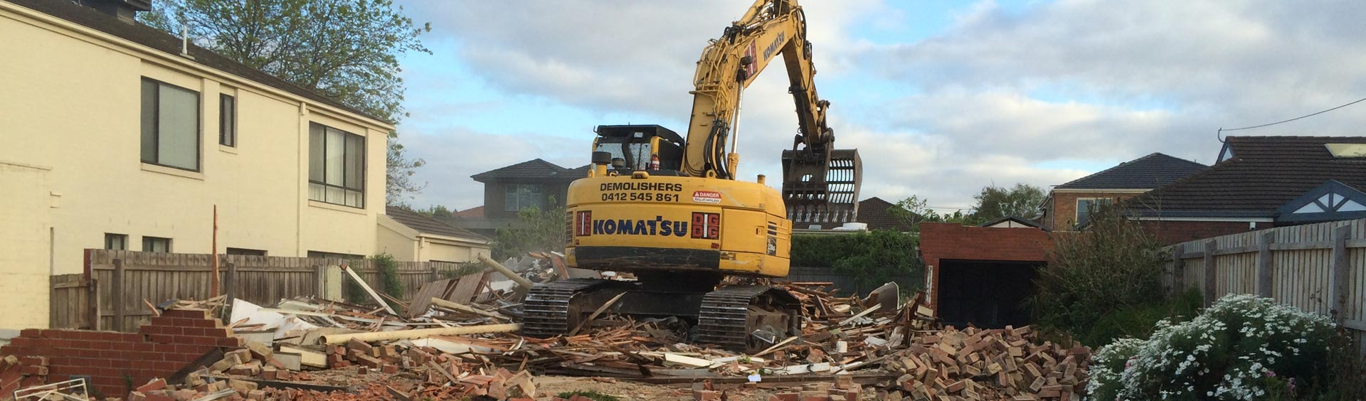backhoe at house demolition site